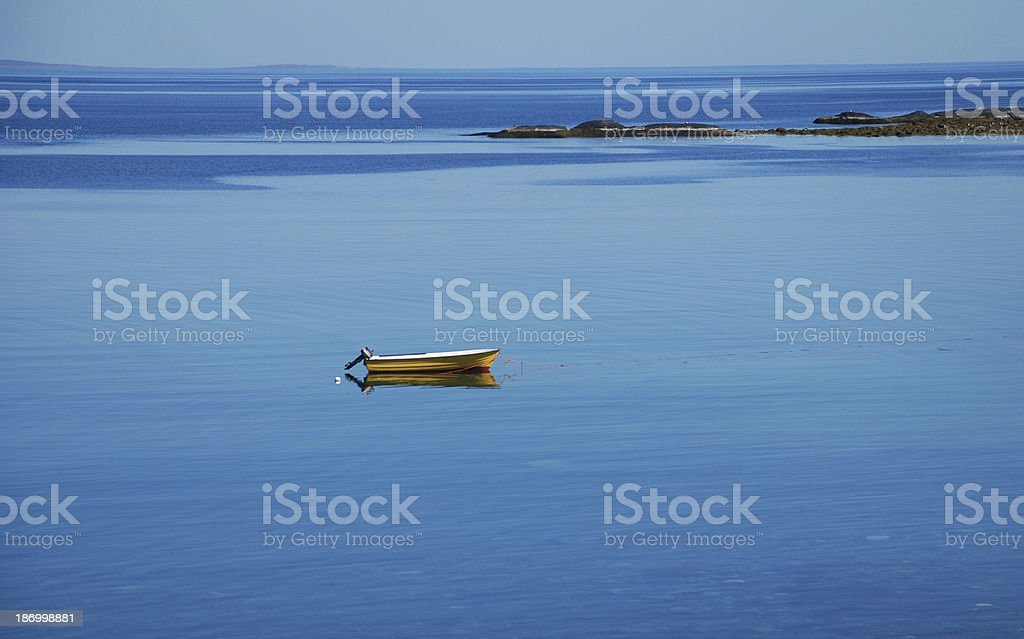 Lonely yellow boat in the blue sea stock photo