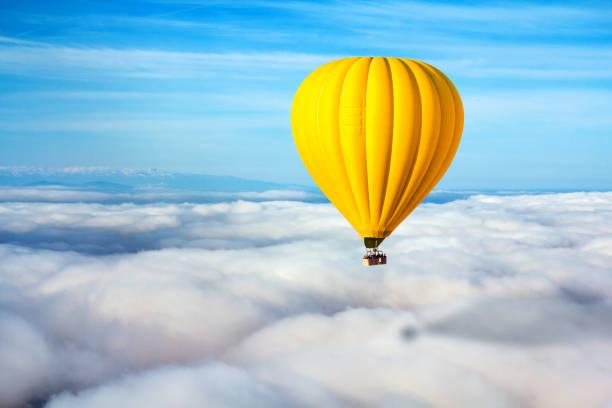 une montgolfière jaune solitaire flotte au-dessus des nuages. leader concept, solitude, réussite, victoire - montgolfière photos et images de collection