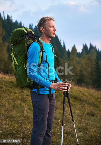 istock Lonely young man hiking with backpack outdoors. 1312960527