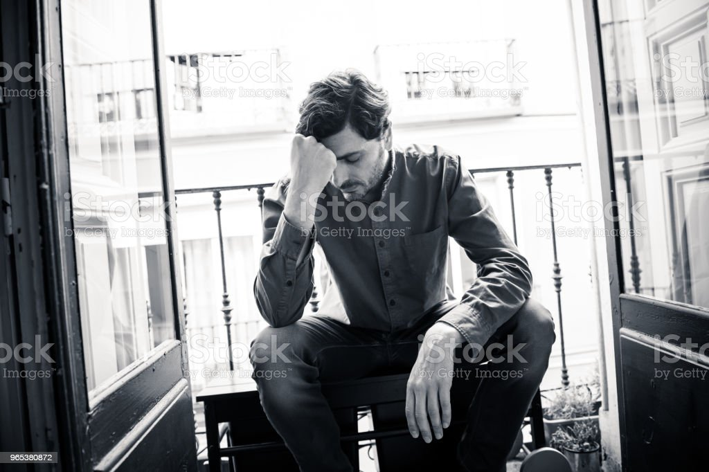 Lonely young man looking outside house balcony looking depressed, destroyed, sad and suffering emotional crisis and grief thinking of taking a difficult and important life decision royalty-free stock photo