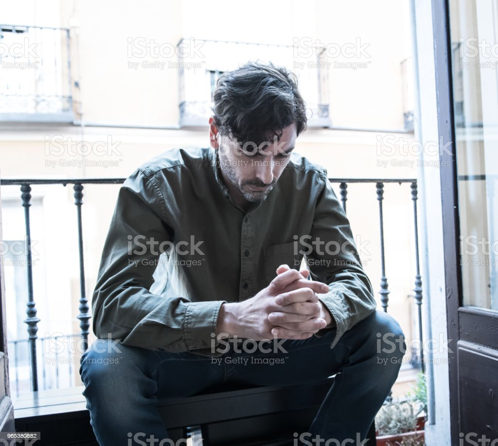 Lonely young man looking outside house balcony looking depressed, destroyed, sad and suffering emotional crisis and grief thinking of taking a difficult and important life decision zbiór zdjęć royalty-free