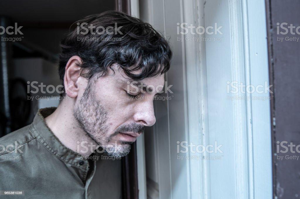 孤獨的年輕人看著外面的陽臺看著鬱悶, 毀了, 傷心和痛苦的情緒危機和悲痛的思考採取了艱難而重要的人生抉擇 - 免版稅40多歲圖庫照片