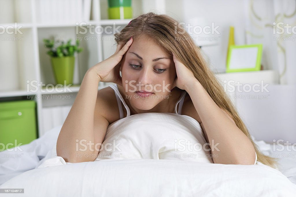lonely young woman lying in bed royalty-free stock photo