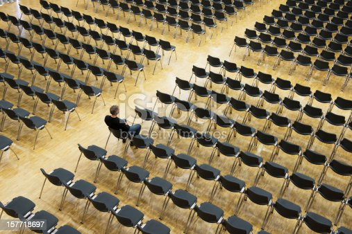 Single mature male person sitting in an auditorium. The rows of the chairs form a cross shape. Great symbol for christianity and loneliness.
