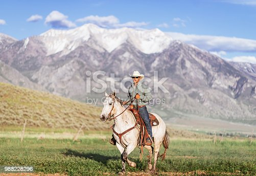 Group of horsemen - cowboys and cowgirls riding horses on the ranch