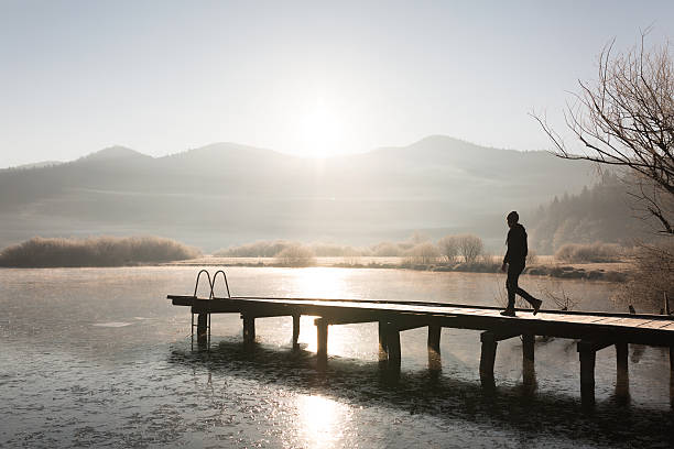 Lonesome man on vacation walks on a jetty at sunrise stock photo