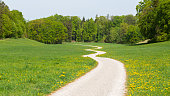 Andechs, Bavaria / Germany - Apr 24, 2020: Long and winding road leading away from the viewer into the woods. Zig zag path with green meadow. Concept for hope, unknown, curiosity. Bavarian landscape.