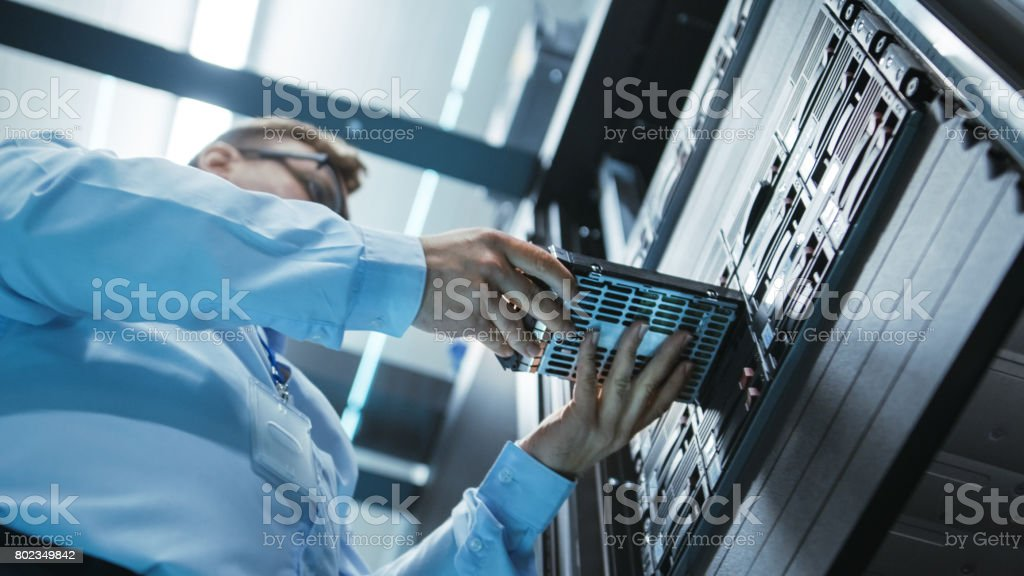 Long Angle Shot In Fully Working Data Center of IT Engineer Installing Hard Drive into Server Rack. Detailed and Technically Accurate Footage. stock photo