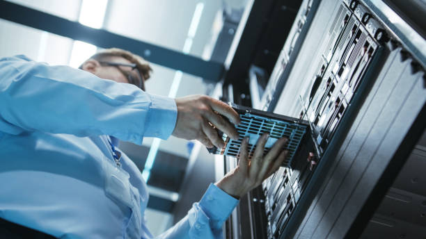 サーバー ラックへのハード ドライブのインストール エンジニア角度それ完全に作業データ ・ センターでのショットに長い。詳細かつ技術的に正確な映像。 ストックフォト