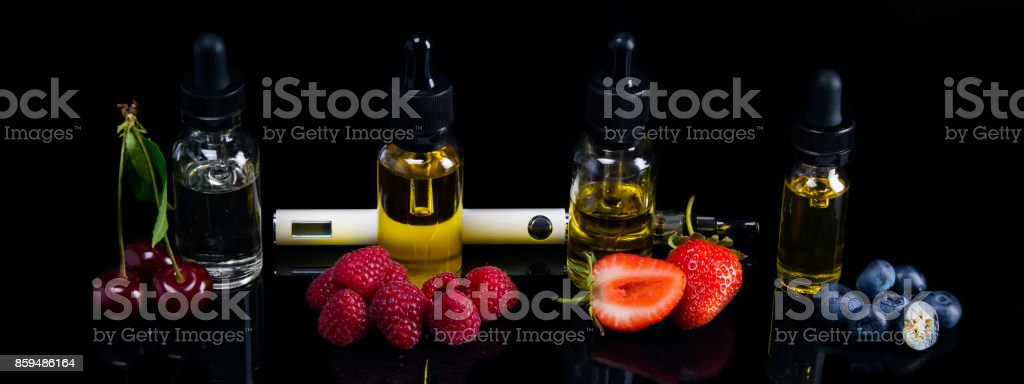 A long background of juicy berries of cherries, strawberries, blueberries and raspberries, on black with a hatching. Next to an electronic cigarette, and the fluidity for it stock photo