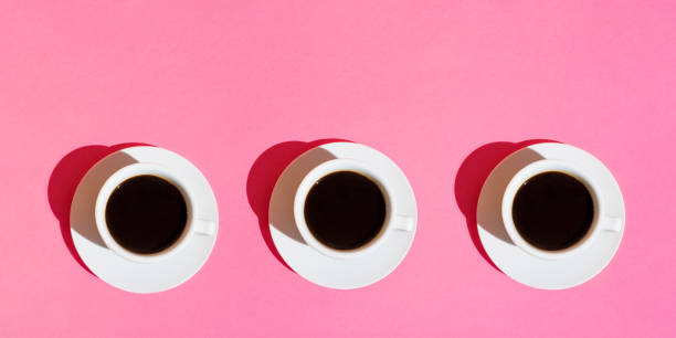 long banner for cafes bars. white cups of coffee with saucer on neon fuchsia pink color background. top view. morning breakfast energy caffeine addiction concept. trendy minimalist. hard sunlight. 80s - pop art foto e immagini stock