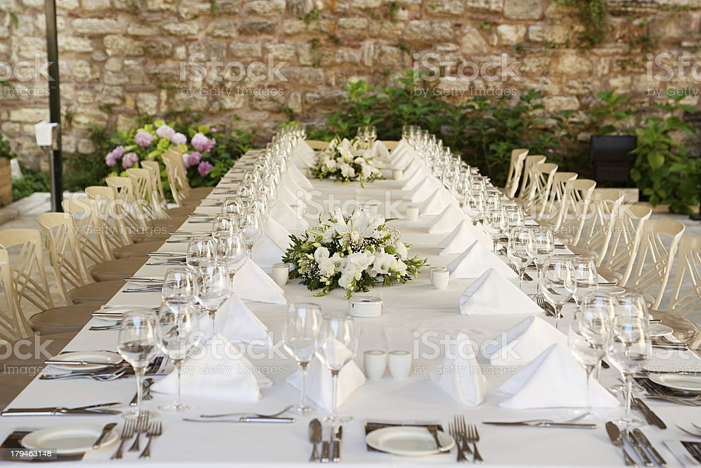 Long banquet table with white settings and centerpieces stock photo