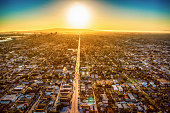 The sun nearing the horizon over Long Beach, California lining up with one of the main streets in the city illuminating the pavement shot from about 1000 feet overhead.