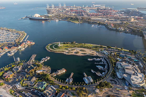 Long Beach Rainbow Harbor Aerial View Long Beach, California, USA - August 16, 2016:  Afternoon aerial view of Rainbow Harbor, tour ships, aquarium and Queen Mary attractions.   long beach california stock pictures, royalty-free photos & images