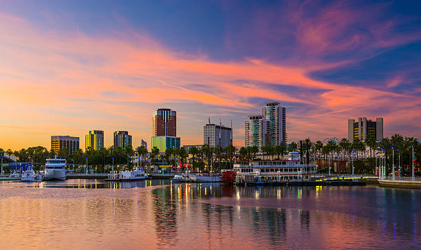 Long Beach skyline at sunset with a dramatic sky Long Beach downtown skyline and Rainbow Harbor at sunset with a dramatic pink, blue, and yellow sky. long beach california stock pictures, royalty-free photos & images
