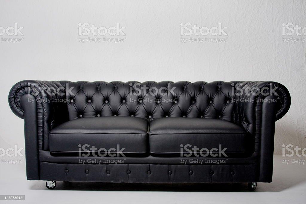 Long black leather sofa on white background stock photo