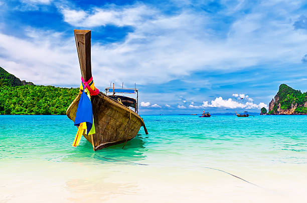 long boat and tropical beach, andaman sea, thailand - phuket stock photos and pictures
