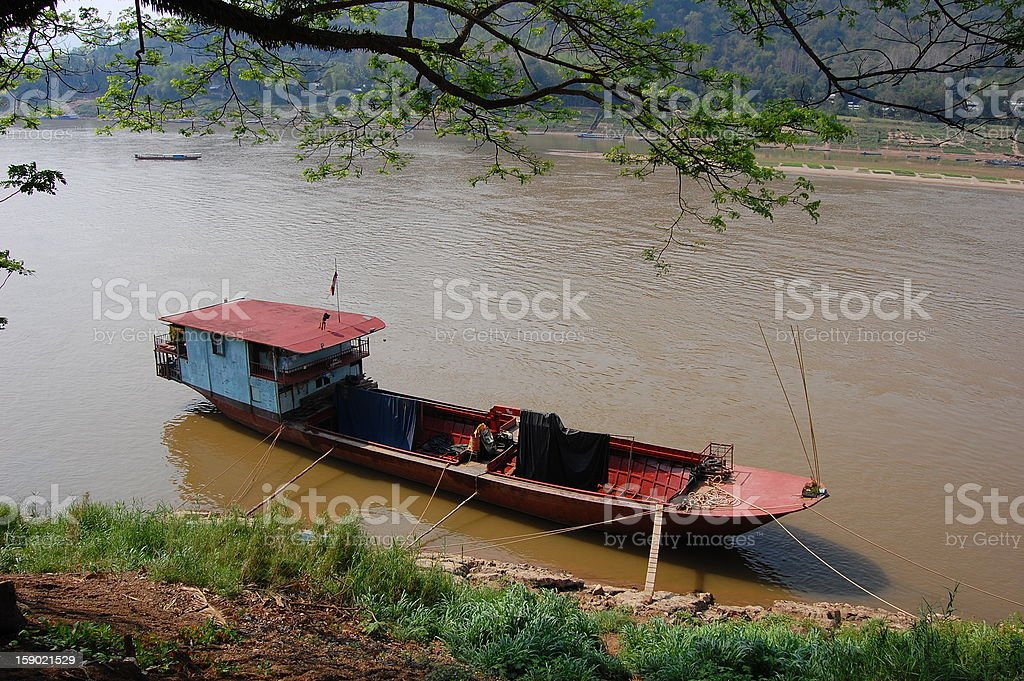 A long boat floats on the Mekong River in Laos. royalty-free stock photo