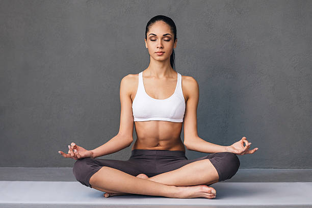 Long breath in. Beautiful young African woman in sportswear practicing yoga while sitting in lotus position against grey background lotus position stock pictures, royalty-free photos & images