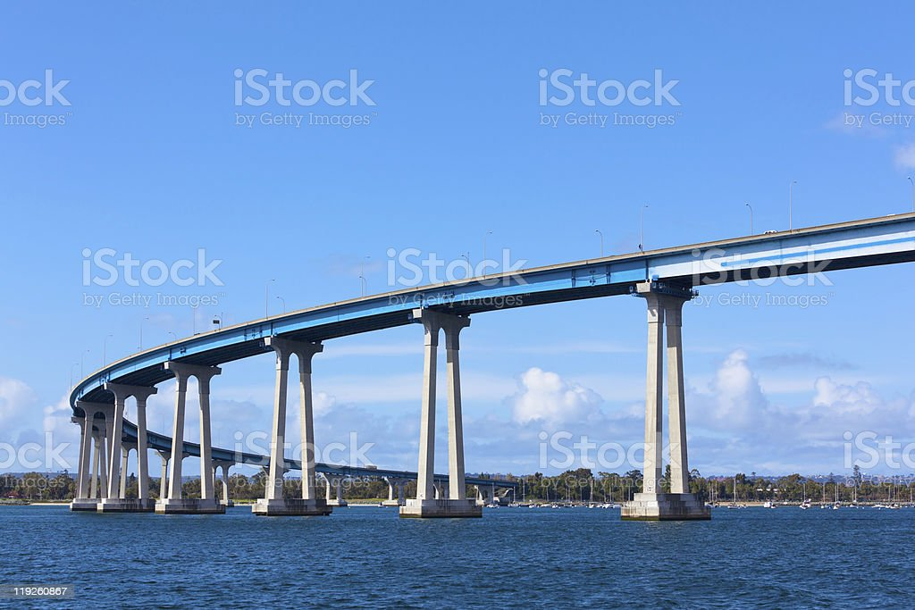 Long bridge crossing a water stream and curving right stock photo