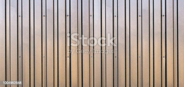 A long abstract background of brown (with shadow black lines) aluminum corrugated sheet metal.