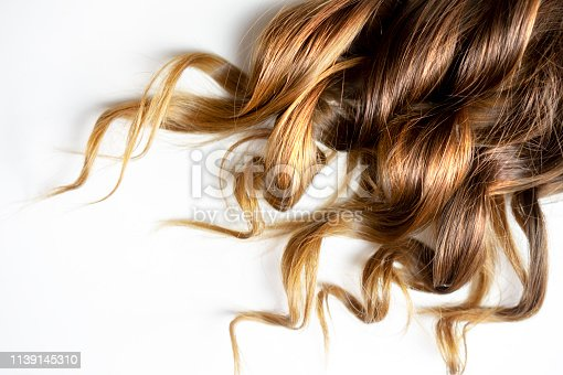 piece of brown curly shiny hair on white isolated background