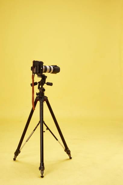 Long camouflaged professional supertele on tripod stock photo