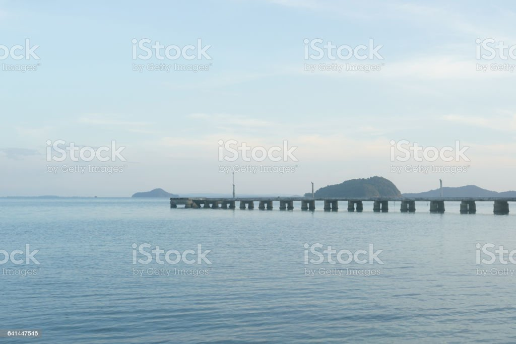 Long concrete jetty with islands and sky background stock photo