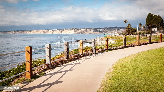 Long concrete walking path along the coastal cliffs of La Jolla, California on a bright sunny day.