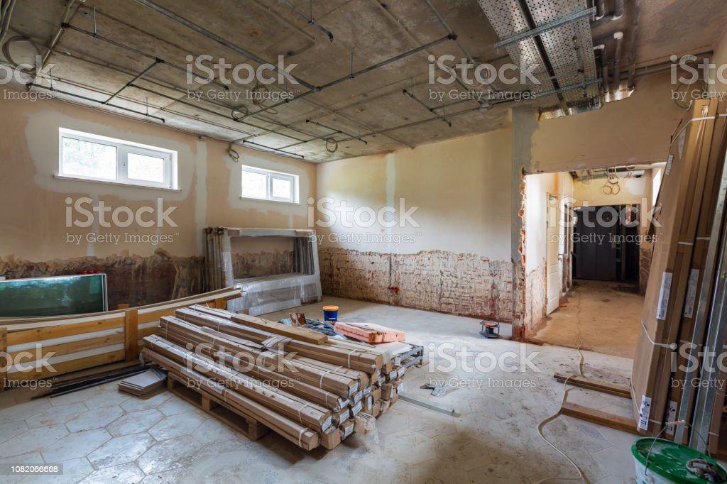 Langer Flur und Zimmer mit Baumaterialien, Kabeltrassen und Wände mit nicht installierten elektrischen Leitungen in einer Wohnung im Bau, Überholung, Umbau, Umbau, home Verbesserungen und Renovierung. – Foto