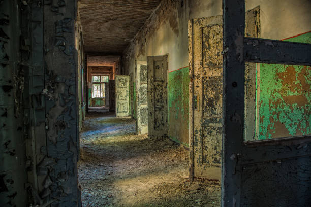 A long corridor with many open doors of a lost place stock photo