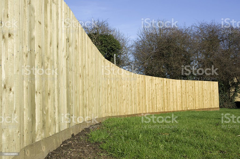 Long curving close boarded wooden fence royalty-free stock photo