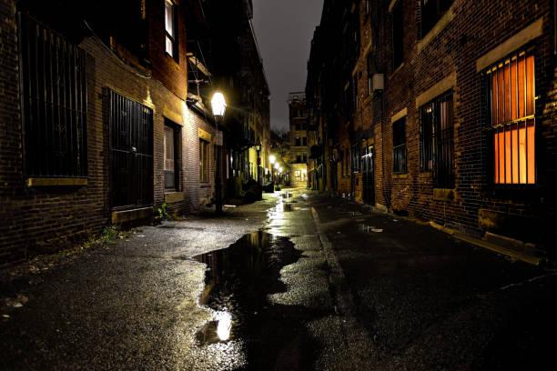 Long dark urban alley between two old buildings stock photo