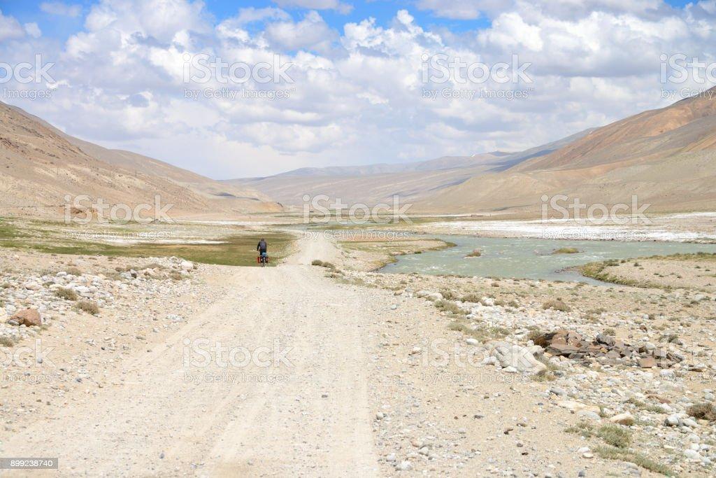 Long distance cycling in the Wakhan valley, Pamir Mountain Range, Tajikistan stock photo