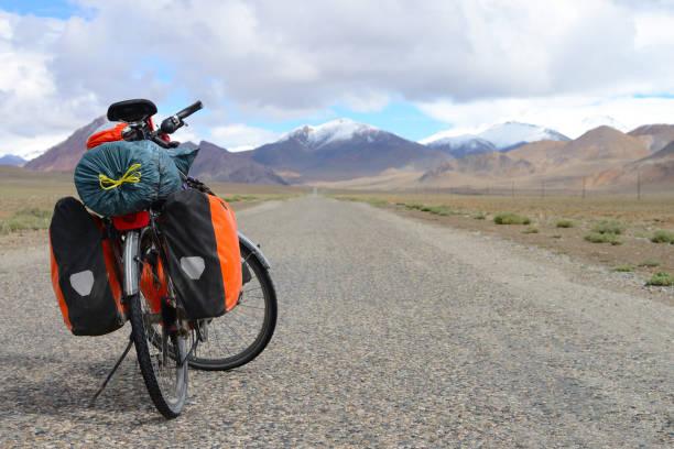 Long distance cycling on M41 Pamir Highway, Pamir Mountain Range, Tajikistan stock photo