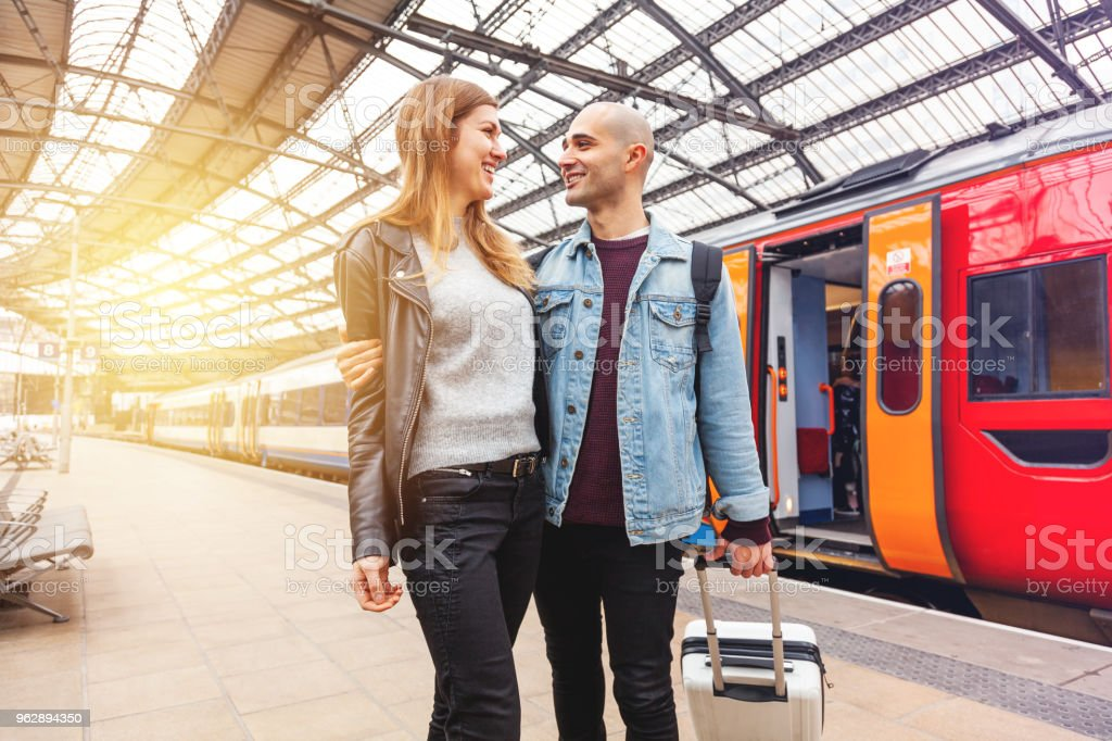 Long distance relationship Young couple together at train station Adult Stock Photo
