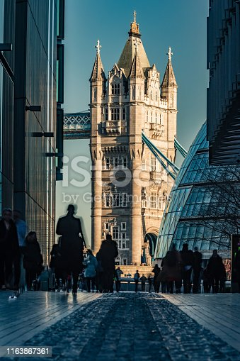 Beautiful sunlit Tower Bridge in City of London, England as viewed from distance through a long lens. Long exposure technique to capture the blurred silhouettes of commuters and tourists with the iconic background of the famous international landmark, connecting City of London directly to the Southwark bank (Unesco heritage site nowadays and build in 1894). Shot on Canon EOS R full frame system with premium RF lens for highest quality results from a tripod.