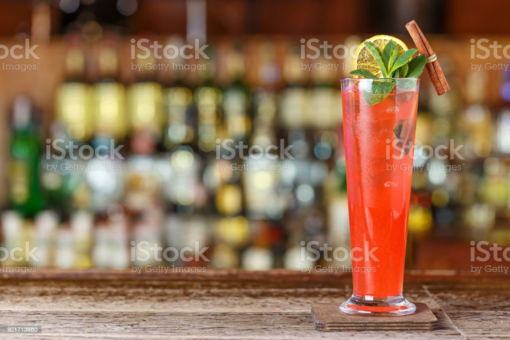 Long Drink fruit sling is on a bar counter on a blurry background of bottles with alcohol in a nightclub. stock photo