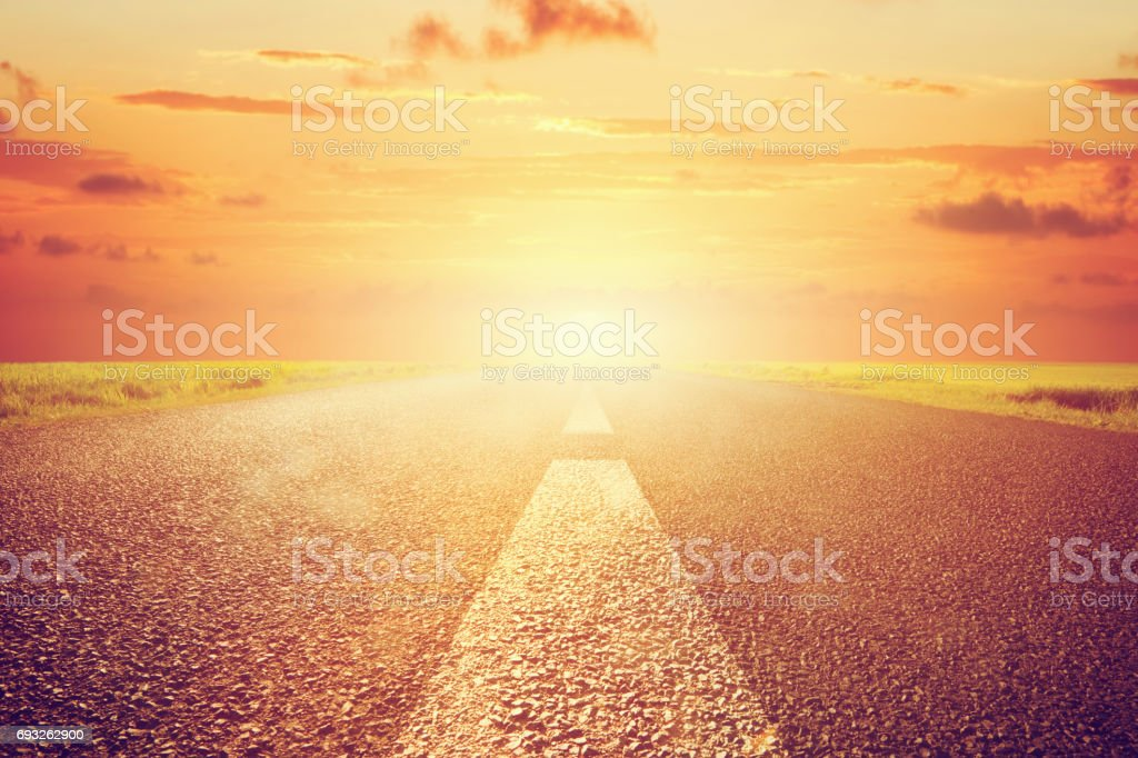 Long empty asphalt road towards sunset sun. stock photo