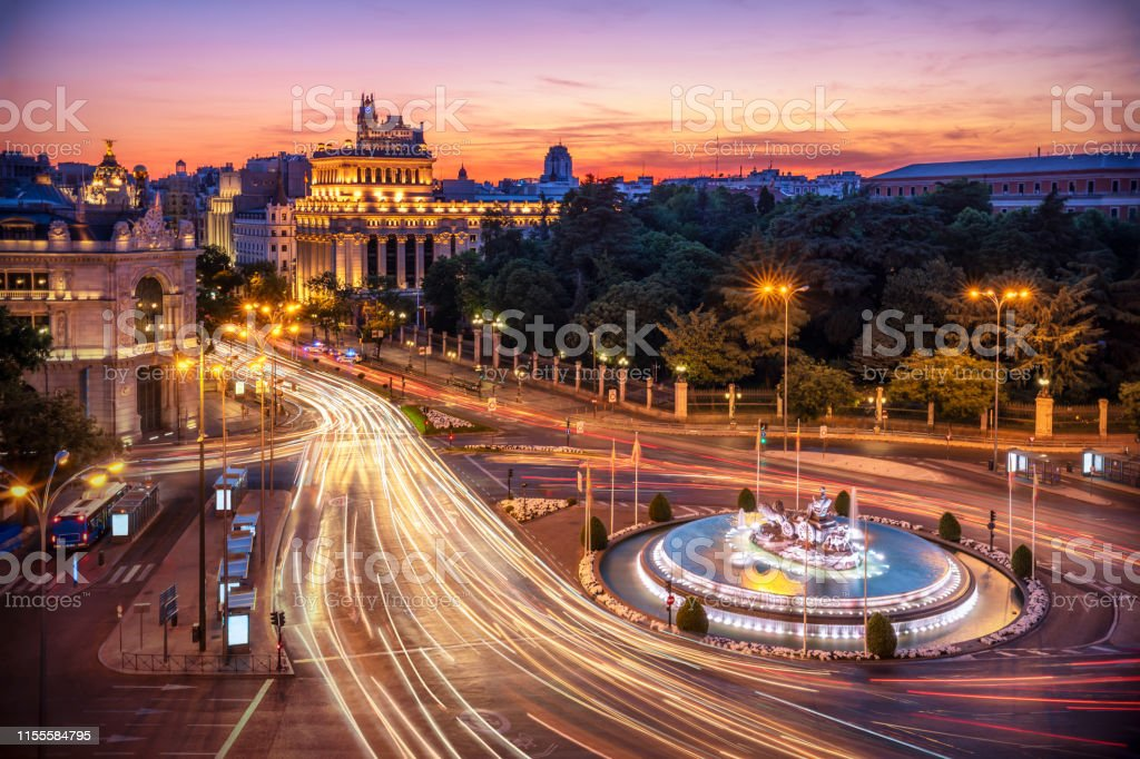 Long exposure Aerial view and skyline of Madrid with cibeles Fountain at dusk. Spain. Europe Aerial view of Madrid skyline at dusk with car light trail around cibeles fountain. Madrid, Spain Aerial View Stock Photo