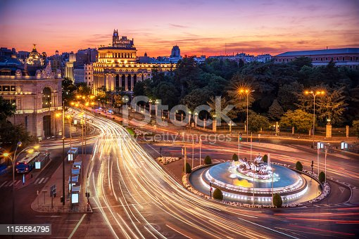 Aerial view of Madrid skyline at dusk with car light trail around cibeles fountain. Madrid, Spain