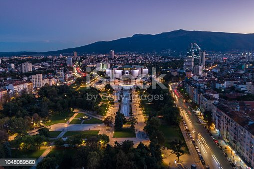 Long exposure aerial view of public park in downtown district in Sofia, Bulgaria at dusk. The scene is situated in downtown district of Sofia, Bulgaria (Eastern Europe) during sunset / dusk / night. The picture is taken with DJI Phantom 4 Pro drone.