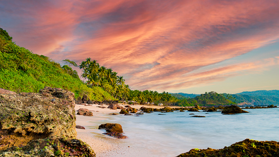 Long exposure. Beautiful and relaxing beach flanked by green palm trees at sunset. Varkala, Kerala, India.
