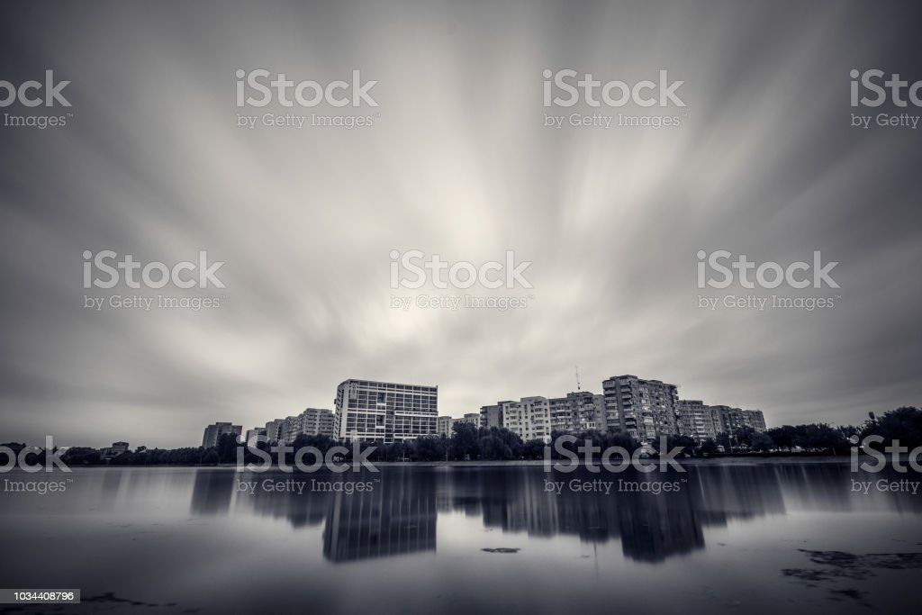 Long exposure cityscape with reflections in a lake with dramatic clouds black and white stock photo