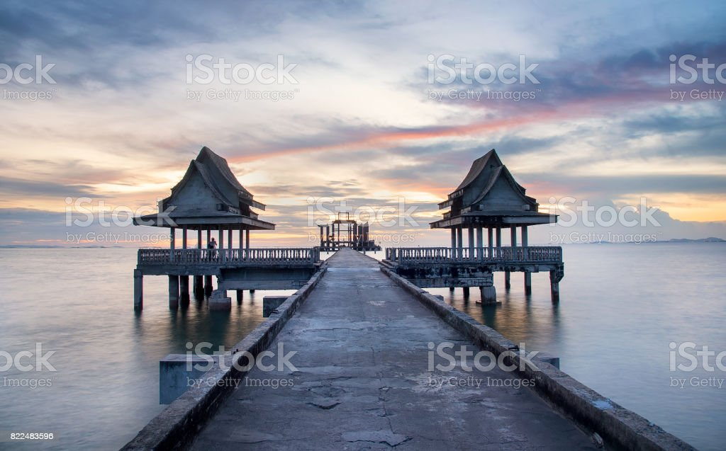 Long exposure image of  pier at sunset blurs the ocean and bathes the structure in the warm glow of the setting sun stock photo