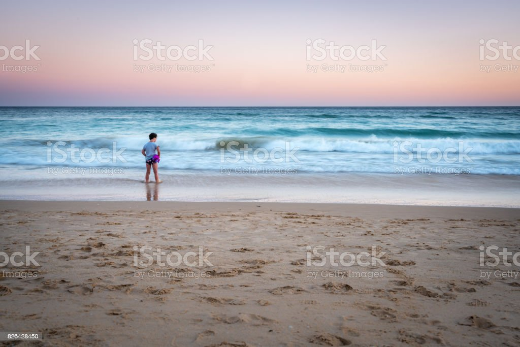 Long exposure image of young girl standing on a beach with waves, sunset in Portugal. stock photo