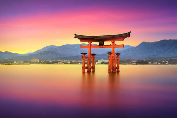 Long exposure itsukushima shrine miyajima floating torii gate, Hiroshima, Japan 25 march 2019 - Itsukushima, Japan:  Long Exposure photo at sunset with the Floating Torii Gate of Itsukushima Shrine off the coast of Miyajima Island. The shrine dates from the mid-16th century shinto shrine stock pictures, royalty-free photos & images