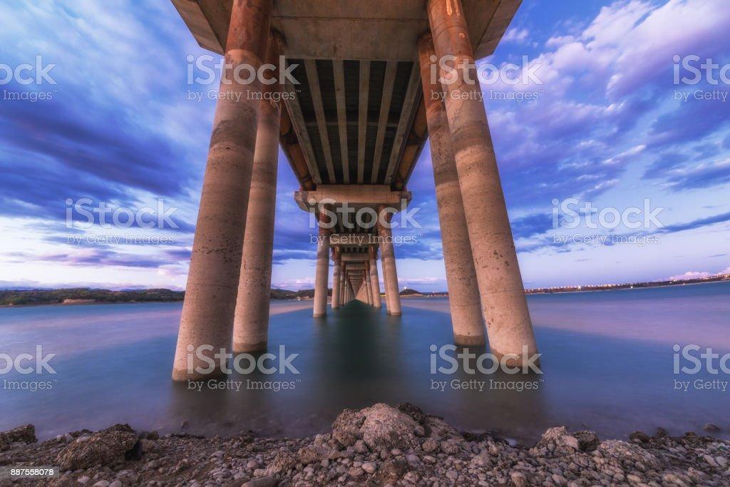 A long exposure landscape of beautiful burning sunset under the bridge stock photo