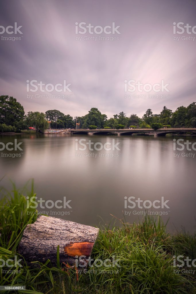 Long exposure landscape scene in a park on a cloudy day with dramatic clouds and a wooden log in the foreground stock photo