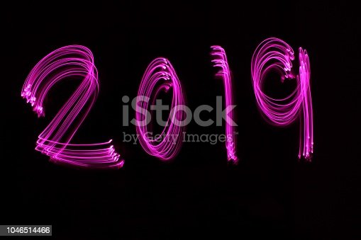 istock Long exposure, light painting photography, 2019 numbers in vibrant pink color against a black background 1046514466